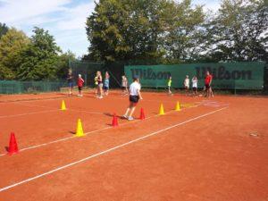 Kids spielen Spiel mit Hütchen auf dem Tennisplatz